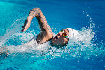 Female front crawl swimmer with tattoos