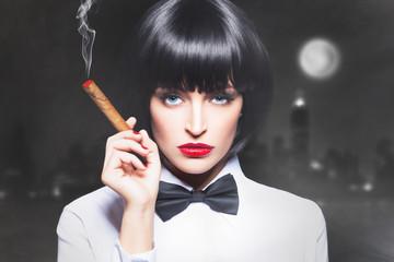 Sexy mafiosi woman boss in tux smoke with cigar