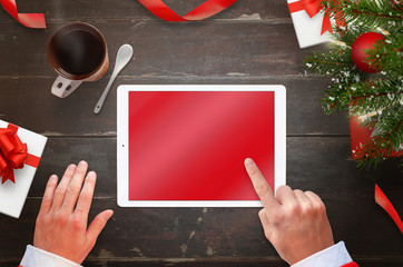 Santa Claus work on tablet with blank screen for mockup. Top view of desk with Christmas decorations.