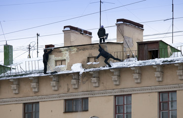 Take off the snow and icicles from the roof. Working cleaning work without insurance. Russia, St. Petersburg