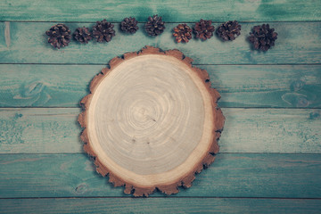 Round boardRound board with pine cones on old wooden background. Top wiev