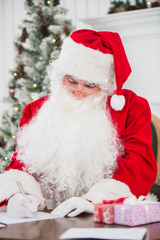 Santa Claus sitting at table and writing on paper