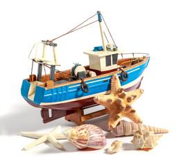 Модель рыболовного судна вместе с ракушками на белом фоне