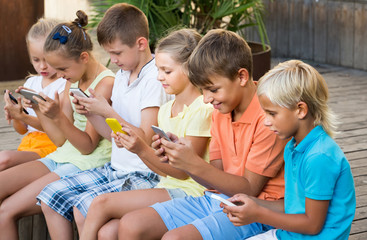 children in school age looking at mobile phones and sitting outd