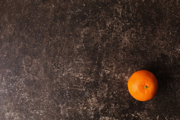 Ripe orange tangerine lies on a dark marble table with scratches. Juicy fruit. Flat lay