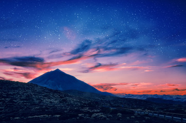 Silhouette of volcano del Teide against a sunset sky. Pico del Teide mountain in El Teide National park at night. Night landscape background with milky way on the sky. Tenerife, Canary Islands, Spain