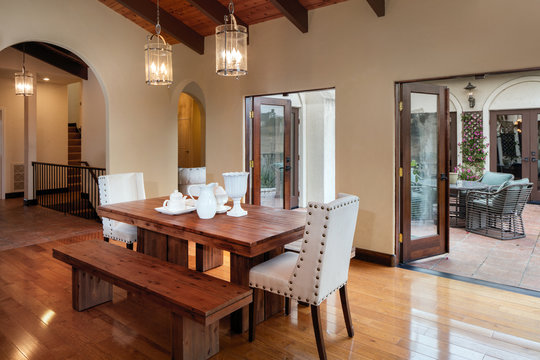 Table and open french doors in dark wood  n mediterranean style