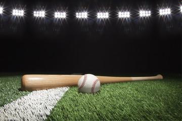 Baseball and bat at night under stadium lights on grass field Wall mural