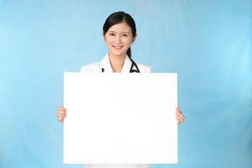 ホワイトボードを持つ笑顔の女医