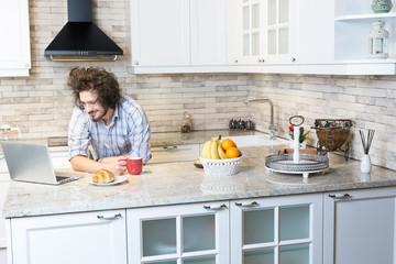Man Eating Breakfast  Using Laptop, Man in kitchen drinking coff