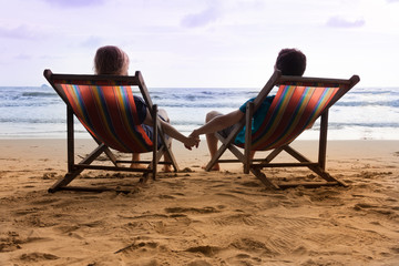 Honeymoon at sunset tropical beach in Thailand. Romantic couple are sitting in deck chairs and holding their hands.
