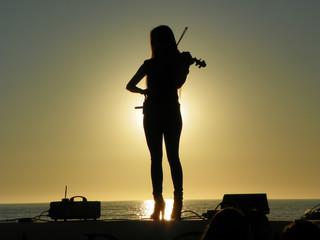 La muchacha brinda un concierto de violín a orillas de la playa.