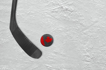 Canadian hockey stick and puck on the ice hockey rink
