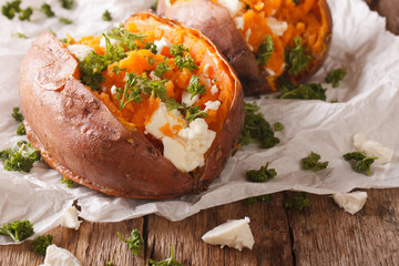 healthy food: baked sweet potato stuffed with cheese and parsley close-up. Horizontal