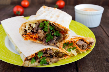 Shawarma sandwich - fresh roll of thin lavash (pita bread) filled with grilled meat, mushrooms, cheese, cabbage, carrots, sauce, green. Traditional Eastern snack. On a dark wooden background.