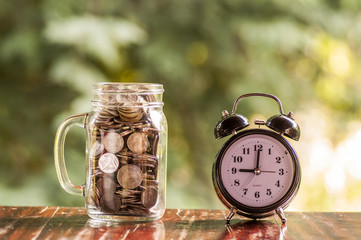 Coins in jar with alarm clock on wooden table with natural background, Money saving concept