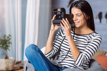 Pleasant young woman taking pictures at home