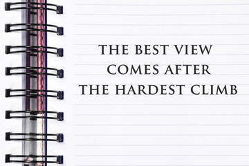 Inspirational motivating quote on spring white note book. the best view comes after the hardest climb.