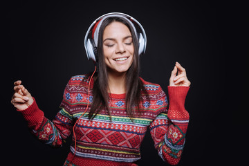 Cheerful young woman listening to the music and dancing