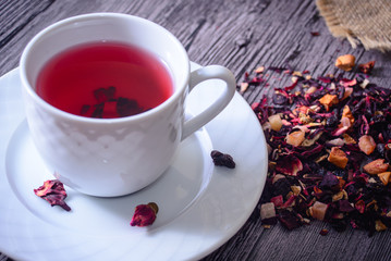 Cup of tea mix of leaves, fruits and dried fruits on rustic back