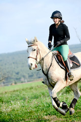 beautiful young woman riding horse and training for jump hurdle equitation competition outdoor
