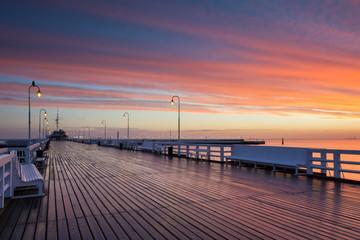 Fototapeta premium Molo w Sopocie w czasie wschodu słońca z niesamowitym kolorowym niebem. Polska. Europa.