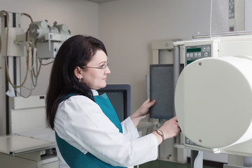 A brunette female doctor working with x-ray machine