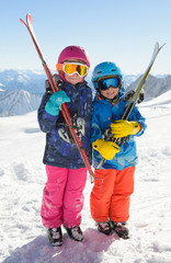 Smiling children  enjoying winter vacations in mountains . Ski,Sun, Snow and Fun.