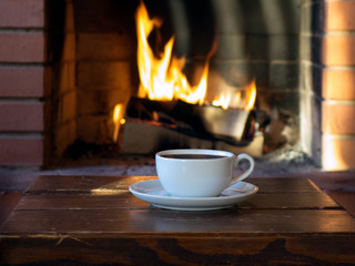 cup of coffee or tea on a background of a burning fire in the fireplace