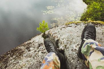 Male feet in camouflage pants near lake