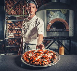 Wall Mural - Young male cook holding fresh cooked pizza on white plate