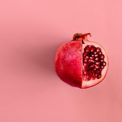 Red pomegranate fruit on pastel pink background. Minimal flat la