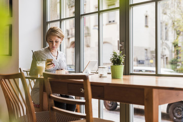 Young woman with cell phone and tablet in a cafe