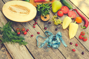 Fruits, vegetables and in measure tape in diet on wooden background. Top view. Toned image.