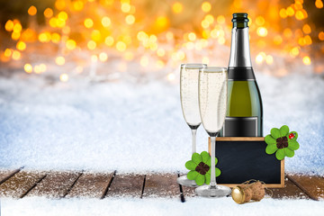 2017 Silvester new years eve bokeh background with champagne bottle glasses empty blackboard decorated with four leaf clover and ladybug