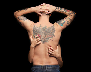 Tattooed man with a woman hands on  back, black background
