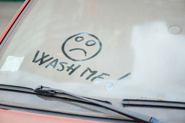 """Dirty car with """"Wash me"""" written on the wind screen"""