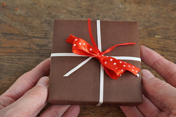 Male hands holding a small brown gift box wrapped with white ribbon and red dotted bow on the wooden background as a symbol of giving and getting presents