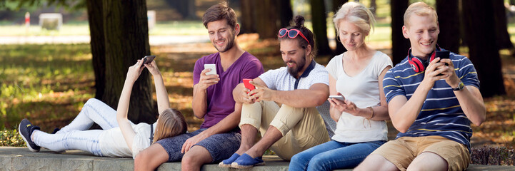 Young people with smartphones in park