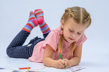 Little girl lying on the floor writing letter