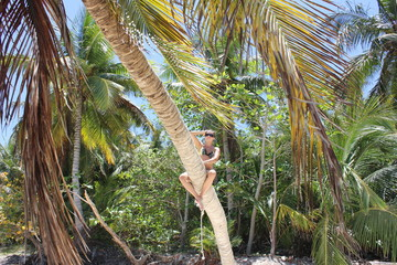 girl climbs a palm tree