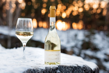 Love, romance, holiday, New Year celebration concept. Bottle and glass of white wine chilled by snow in winter forest on sunset.