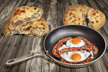 Sunny Side Up Eggs Fried with Bacon Rashers in Old Frying Pan Set on Weathered Garden Table With Two Torn Pitta Bread Loafs