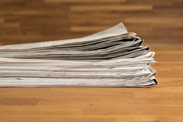 Ein Stapel Zeitungen auf einem Holztisch