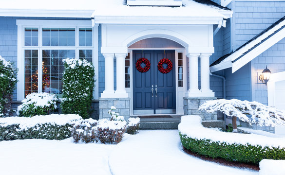 Walkway to home decorated for the winter holidays with snow
