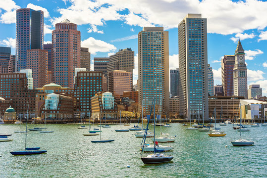 Floating sailboats with the skyline of Boston in the background