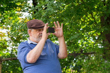 Bearded senior man using cellular phone outdoor making photos with internal camera