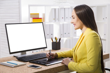 Woman in a yellow jacket drawing at her computer