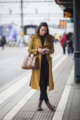 Sweden, Skane, Kirstianstad, Young woman looking at smartphone at train station
