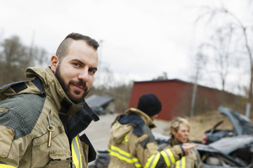 Sweden, Sodermanland, Firefighter looking at camera and others standing beside car